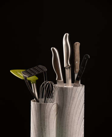 set of knives for the kitchen and various kitchen appliances on a black background