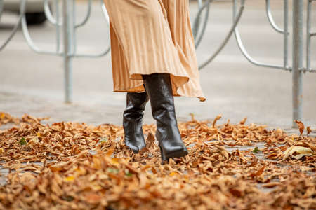 Woman legs in boots and long skirt walking on yellow dry fallen leaves in autumn park