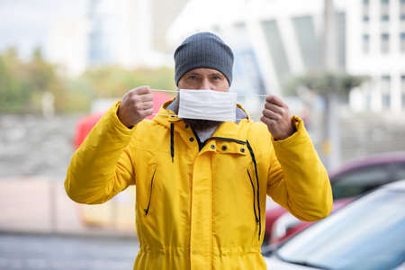 Handsome bearded man looks at the camera and holds a medical mask in front of him. Blurred background. Man on the street doubts whether a mask is needed for protection. Covid pandemic concept. 版權商用圖片