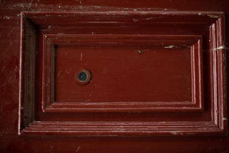 front view closeup of vintage metallic view finder on blown scratched old wooden red door texture