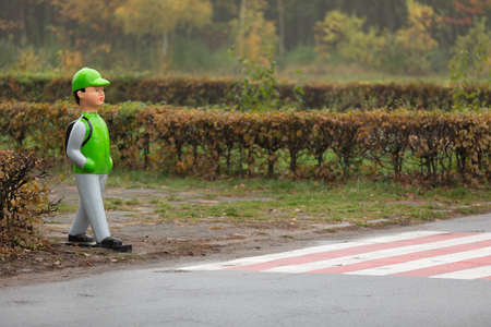 Pedestrian crossing with appropriate road signs and figure-dummy in the form of schoolboy with a backpack. a dummy of a child near a pedestrian crossing, which warns of danger