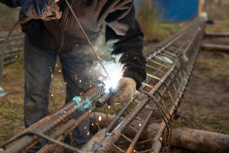 worker is engaged in welding a metal structure in factory.