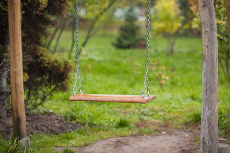 An old wooden swing sitting in a lush backyard. wooden swing on chains at the garden