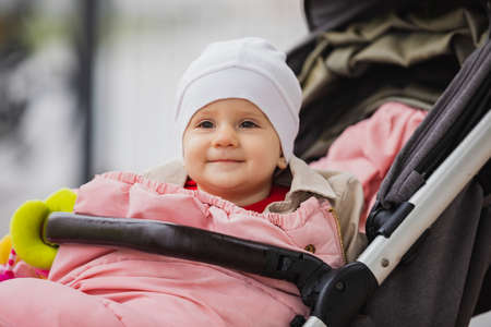 baby sitting in baby carriage, open eyes, in hat and jacket, winter or autumn time. Portrait of child outdoor. 版權商用圖片