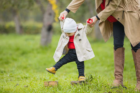 Cute funny happy child making his first steps on a green lawn in autumn garden, mother holding his hands supporting by learning to walk Archivio Fotografico