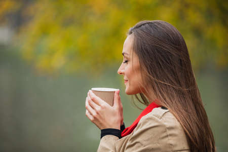 portrait of Brunette woman drinking a coffee in the autumn park. 版權商用圖片