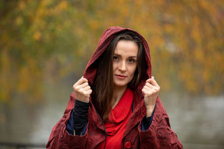 Portrait of a woman in hooded red raincoat walking in park on a rainy autumn day
