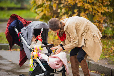 mother is putting small shoes to her Baby in the autumn park. baby sitting in a stroller