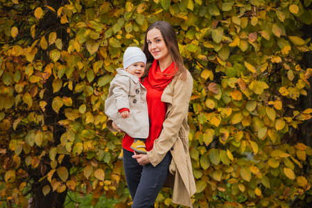 Bay with mom in autumn park. Mom and daughter in the fall. Mom holds the baby in her arms. Mother with her little daughter in the autumn park on a walk. Fall Family walking. 版權商用圖片