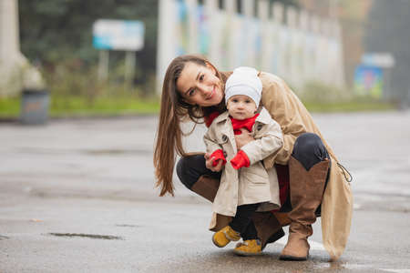 outdoor portrait of a mother with her baby. Mom and daughter walking in an autumn park 版權商用圖片
