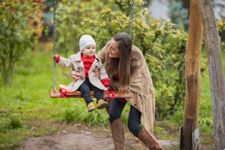 mother shakes her baby on swing at the autumn park. Happy family spend time together. Lifestyle concept