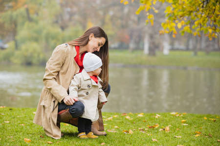 Happy family playing outdoors in park near the lake, Winter, autumn life