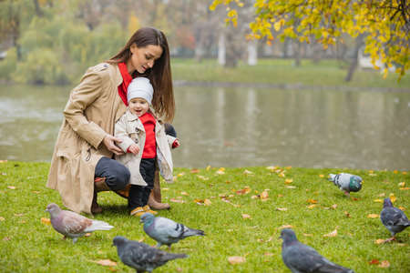 Happy family playing outdoors in park, Winter, autumn life. mom and baby feed the depths of the lake