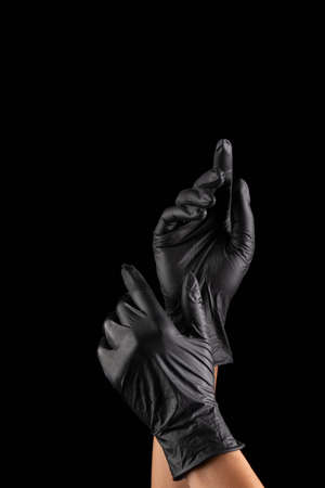 black medical rubber gloves weared at hands on black background 版權商用圖片