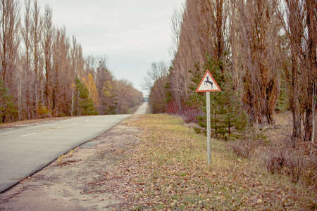 Warning sign when urban road enters forest. Roadsign is in fall colors. Chernobyl road in exclusion zone. Radioactive zone in Pripyat city - abandoned ghost town.