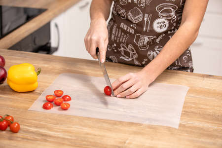 Cutting tomato. woman cuts a cherry tomato in the kitchen 版權商用圖片