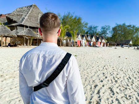 Male tourist walking along the beach in Zanzibar. A man looks at small authentic houses along the beach. travel to an exotic country