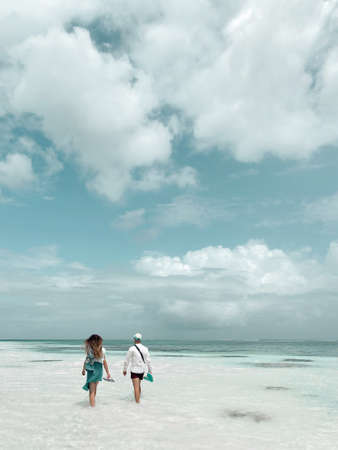 Back view of happy young couple walking on a deserted tropical beach with bright clear blue sky 版權商用圖片