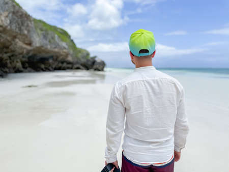 Back view of young man walking on white sandy beach at the ocean in Zanzibar. traveling to an exotic country 版權商用圖片