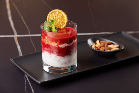 Layered dessert with fruits, nuts and cream cheese in glass