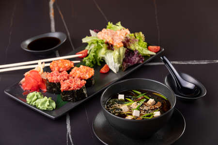 Japanese food, sushi, rolls, soup, salad on black background