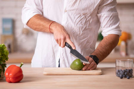 Chefs hands cutting avocado with the help of knife on a white surface