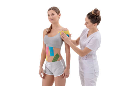 dynamic functional bandage with taping. female specialist glues tapes on the shoulder of woman 免版税图像