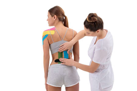 Physical therapist applying tape on female patients lower back. , physical therapy, rehabilitation concept.