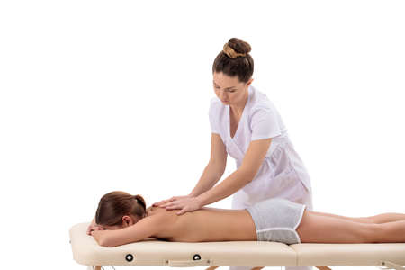 female masseur makes back massage young woman on a special portable massage table isolated