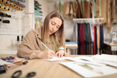 female fashion designer is working in her workshop. Stylish woman in process of creating new clothes collection.
