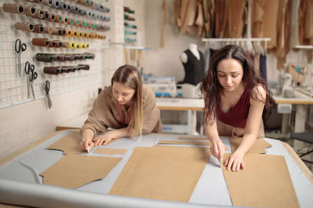 female tailors working with sewing pattern in atelier studio workshop 免版税图像