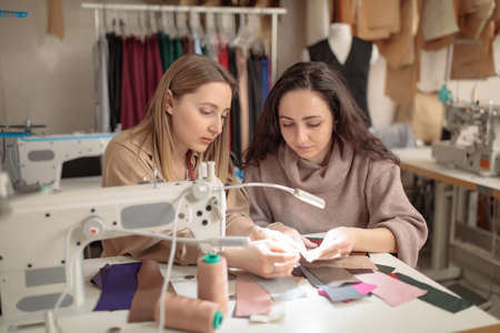 Two female fashion designers were looking at samples of sketches in a sewing workshop