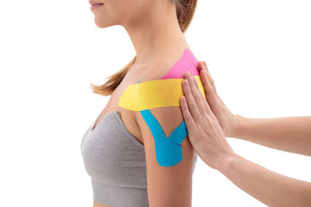 Physiotherapist putting on tape on female patients shoulder isolated over white background 免版税图像