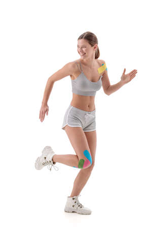taping. Young female athlete isolated on white background with tape on shoulder and knee. Fat lose, sport physical therapy,recovery concept.