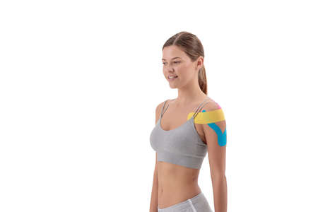 Colored tape on young sportswoman shoulder isolated on white background. Copy space 免版税图像