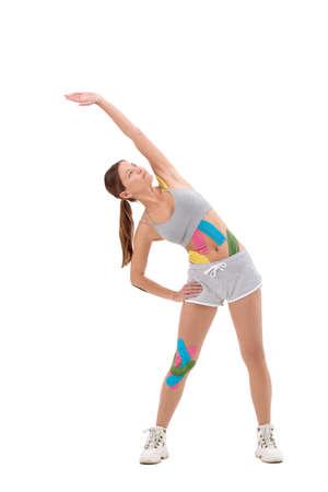 Amazing stronger sports fitness woman make exercises isolated over white background. Tape. Theme tape rehabilitation. Woman with elastic bandage. sport taping.