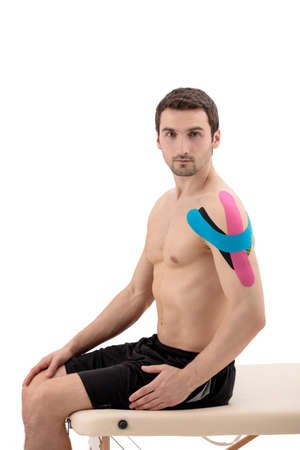 Male shoulder with physio tape, isolated on a white background. Portrait of man with tape on body sitting on a portable massage table