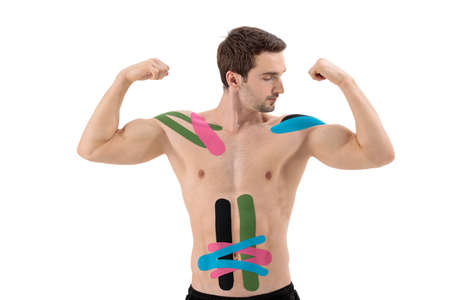 Male portrait of professional athlete with tape on belly and shoulder isolated on white background. Sport and rehabilitation, treatment 免版税图像