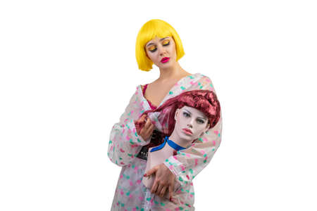 Positive female model holding dummy isolated on white background. Woman wearing in yellow wig