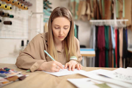 Young female fashion designer drawing sketch with model sitting in her office atelier. 免版税图像