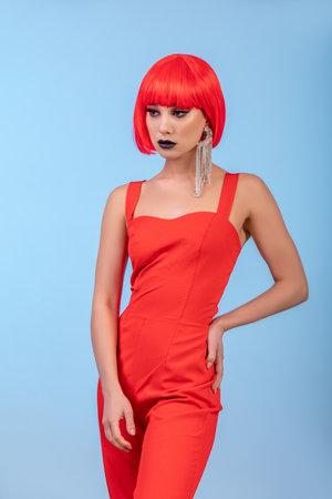 Portrait of Pretty woman in red wig over blue background. long earring 免版税图像