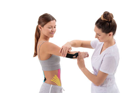 Physiotherapist applying tape on female patient's arm. , physical therapy, rehabilitation concept. Tennis or golfers elbow treatment. isolated on white background