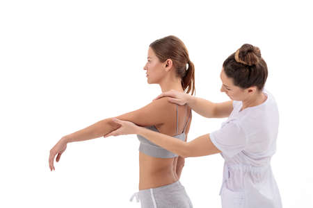 Female Patient at the physiotherapy doing physical exercises with chiropractor isolated on white background 免版税图像