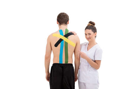Young Woman physiotherapist Applying Special Physio Tape On Man's Back isolated on white background
