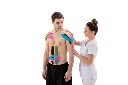 Female physiotherapist putting on  tape on patient's shoulder isolated on white background