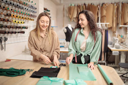 Small business, local production. Two young female colleagues work in their Atelier. entrepreneur and business owner. Packaging for sending products to an online store
