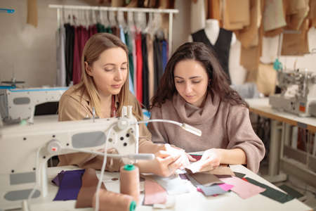 Designers inspecting sample fabric with their hands near the sewing machine in a studio 免版税图像