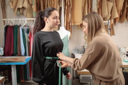 Fashion model fitting clothes by professional designer studio, taking measurements. Tailor workshop