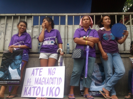 stating: Protest during the oral debate of RH bill at the Supreme Court in Manila. A group of women in violet shirt brings their placard with validation that they are Catholics. Photo shows a woman with placard stating that she is the eldest daughter among 14 kids Editorial