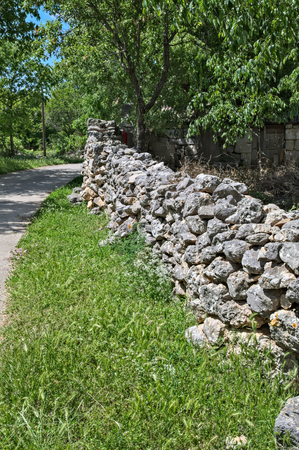 Stone fence beside road made of rocks Stock Photo